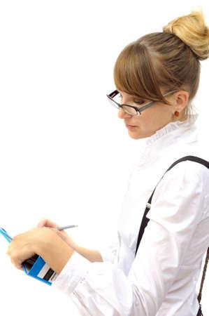 Beautiful businesswoman writes in folder, isolated on white photo