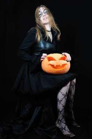 vampira sexy: Sexy chica vampiro con calabaza de Halloween sobre fondo negro