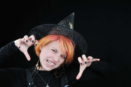 Young beautiful furious halloween witch on black background photo
