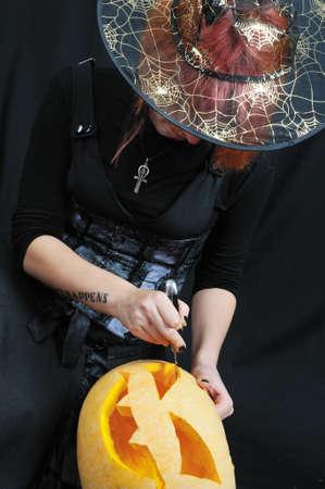 witch prepare pumpkin on black background photo