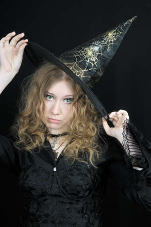 Cute young witch in hat, on black background photo