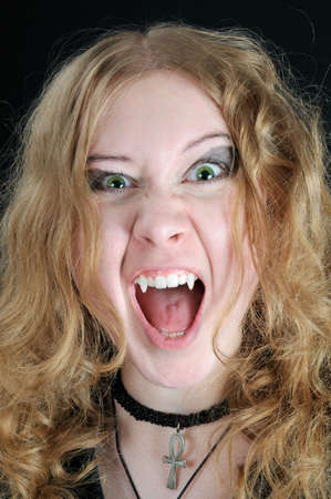 Screaming young vampire girl, on black background photo