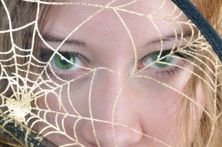wep: Green eyes look through spiders web Stock Photo