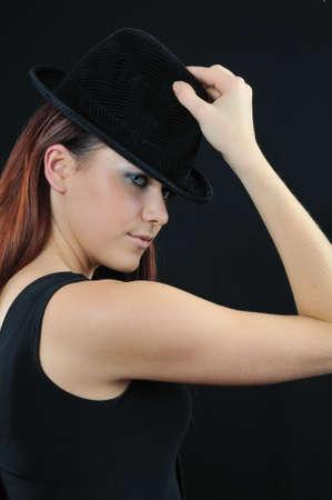 lovely girl in black bonnet on black background photo