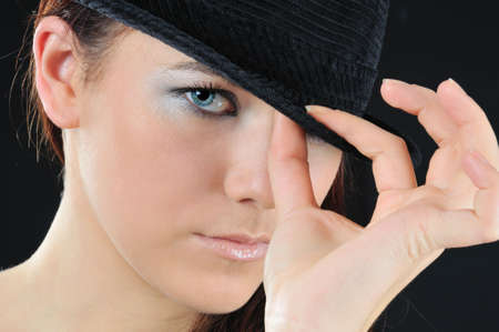 alluring girl hold on the hat two fingers photo
