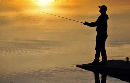"""Sylwetka rybaka w zachodzie sÅ'oÅ""""ca Zdjęcie Seryjne"""