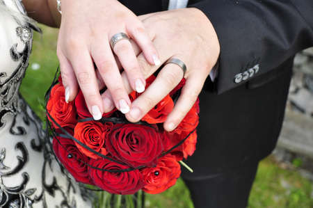 wedding ring hands: Hands with wedding rings and flowers Stock Photo