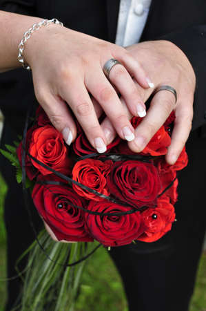 Hands with wedding rings and flowers photo
