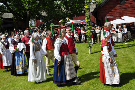 Torsstuna, Sweden-June 19: Folklore ensemble of Sweden in traditional folk costyme perform a dance in midsummer day on June 19, 2009 in torstuna, Sweden. Stock Photo - 12060476