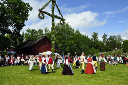 maypole: Torsstuna, Sweden-June 19: Folklore ensemble of Sweden in traditional folk costyme perform a dance in midsummer day on June 19, 2009 in torstuna, Sweden. Editorial