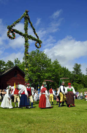 midsummer pole: Torsstuna, Sweden-June 19: Folklore ensemble of Sweden in traditional folk costyme perform a dance in midsummer day on June 19, 2009 in torstuna, Sweden. Editorial