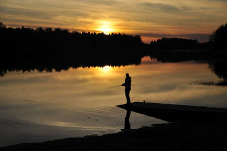 Silhouette of a fisherman at sunset photo