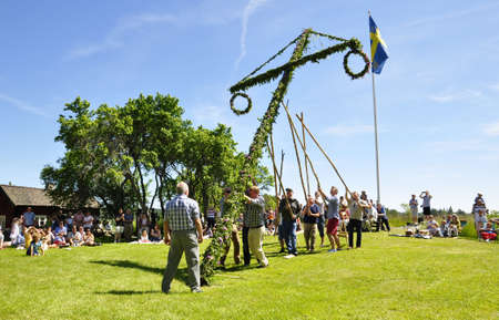 midsummer: Torsstuna, Sweden-June 22: Folklore ensemble of Sweden in traditional folk costyme perform a dance in midsummer day on June 22, 2012 in torstuna, Sweden.