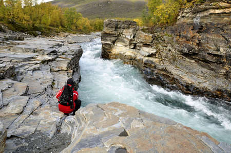 swedish: Abisko canyon in Autumn and a hiker