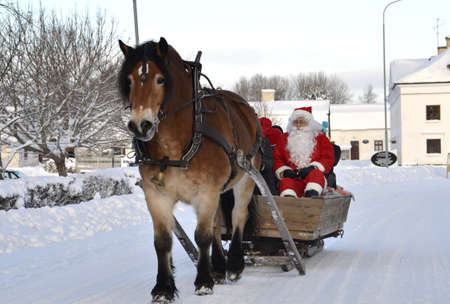 Gysinge, Sweden - December 08: Santa claus goes to sleigh with brown horse at Christmas time in Gysinge on December 08, 2012 in Gysinge Sweden. Stock Photo - 16769554