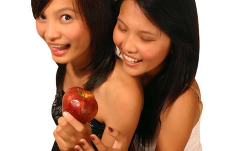 ingest: Two woman with an apple Stock Photo
