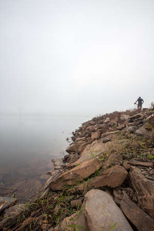 Foggy dams early morning A man stand along dams  photo