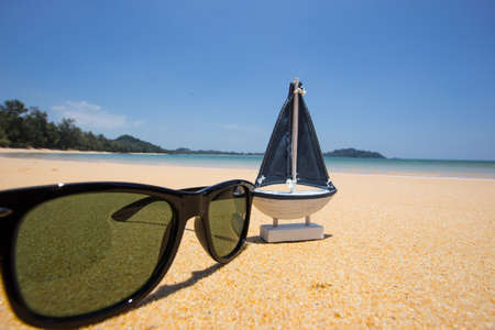glass paper: wooden sail ship toy model and sunglasses  in the sea sand.