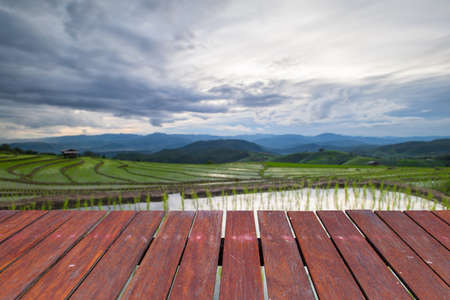 wooden floor and Blured rain cloud moving on Agriculture terrace rice fields on the mountain. Stock Photo