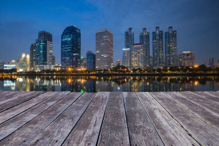 blured: wooden floor and Blured business district and reflection building.