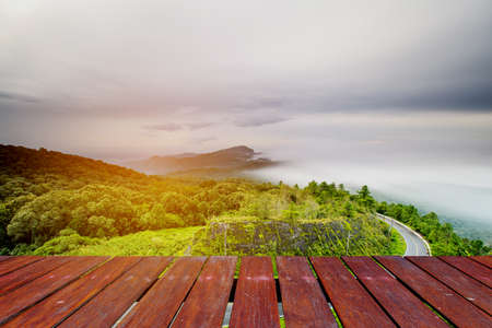 blured: wooden floor and Blured Mountain forest landscape and cloudy Stock Photo