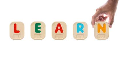 braille: El alfabeto bloquea la ortografía de la palabra aprender con Braille y la celebración de mano N Foto de archivo