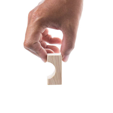 majuscule: Hand holding  Wooden Block on white background.