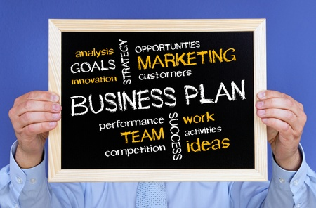 Businessman holding Business Plan Chalkboard photo