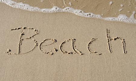sand writing: At the Beach - Summer Holidays Stock Photo