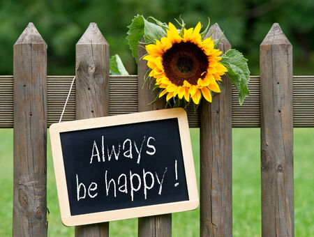 Always be happy text on blackboard hung on fence photo
