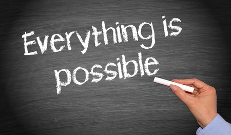 possibility: man writing Everything is possible text on chalkboard Stock Photo