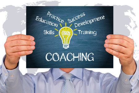 man holding Coaching - Business Concept text