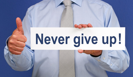 never: Man hold a Never give up board Stock Photo