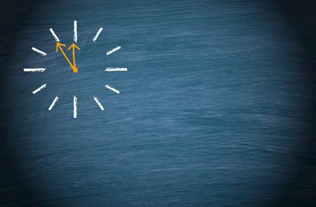 Clock on blue chalkboard background Standard-Bild