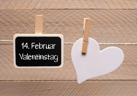 Valentines Day on February 14 written on blackboard hang on a rope photo