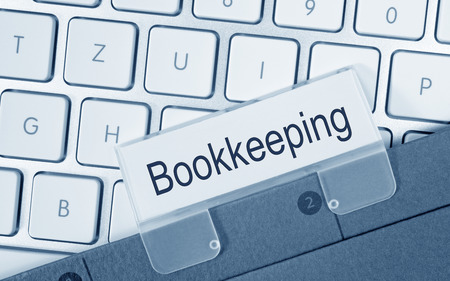 financial management: Bookkeeping - folder on computer keyboard