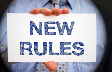 regulations: New Rules - Businessman with sign