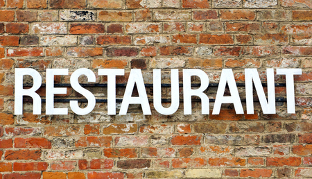 Old Restaurant sign on stone wall Stock Photo