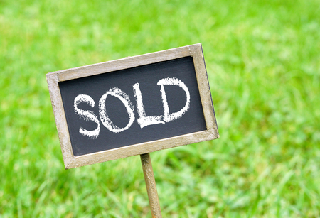 Verkocht - bord op groen gras achtergrond Stockfoto