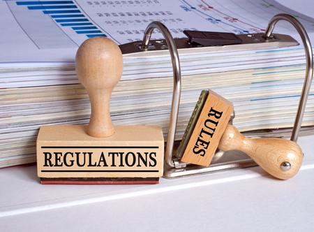 Regelgeving en normen - twee stempels in het kantoor Stockfoto