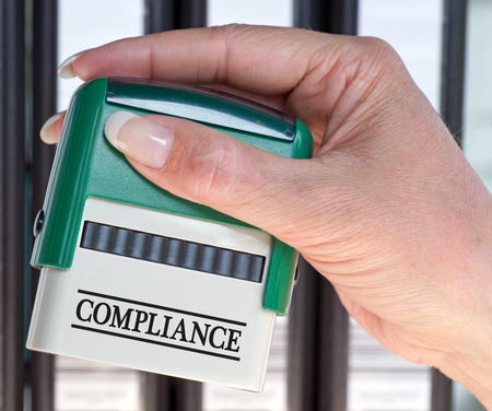 comply: Compliance Stamp with female hand in the office