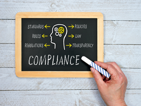 Compliance chalkboard on wooden background Stock Photo