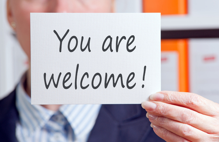 friendliness: You are welcome - Businesswoman with sign Stock Photo