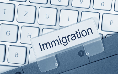 immigrate: Immigration Folder on Computer Keyboard