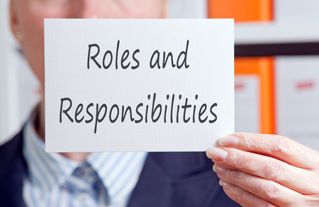 business roles: Roles and Responsibilities - business woman with sign