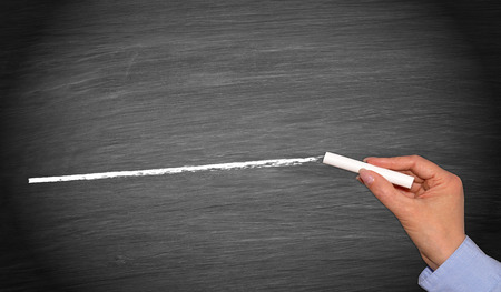 Hand with chalk drawing line on empty chalkboard