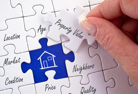 Property Value - female hand with real estate puzzle Stock Photo