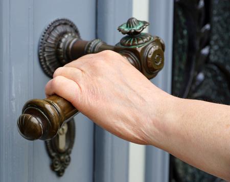 Female hand with old handle bar opening door