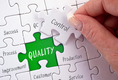 Qualitätskontrolle - weibliche Hand mit Business-Puzzle