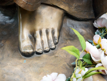 Foot of bronze statue with flowers